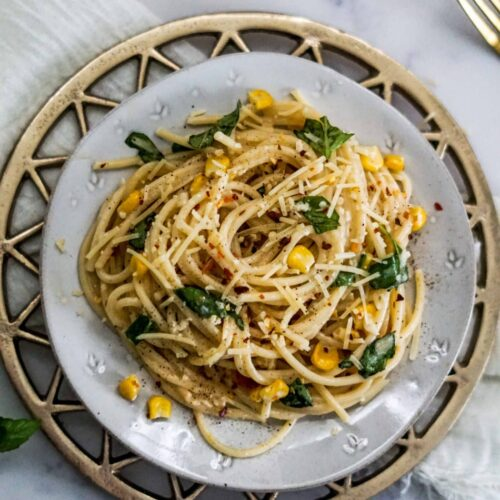 spicy lemon spaghetti in a plate with basil and corn