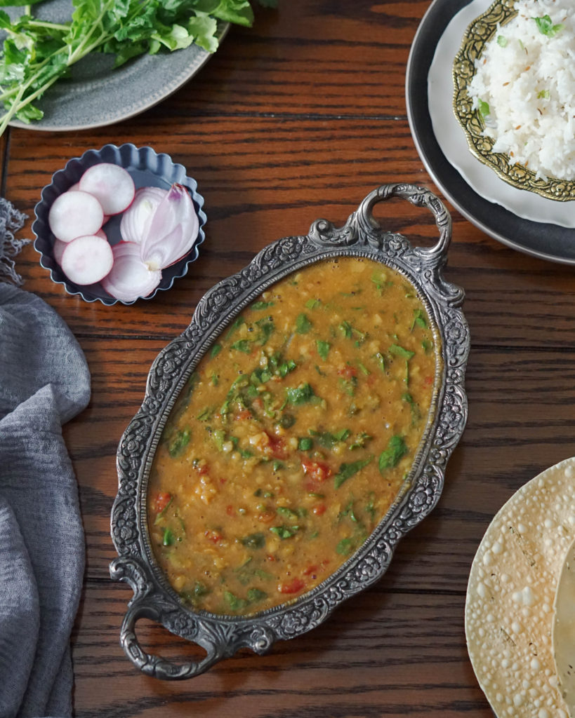 Palak dal or spinach dal in gray bowl with jeera rice and papad on brown table