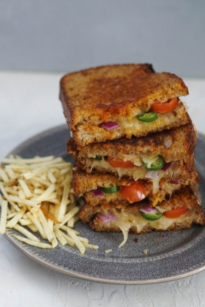 Inside out grilled cheese Stacked grilled cheese with jalapenos, onions and tomatoes