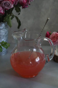Rose lemonade in a pitcher with roses