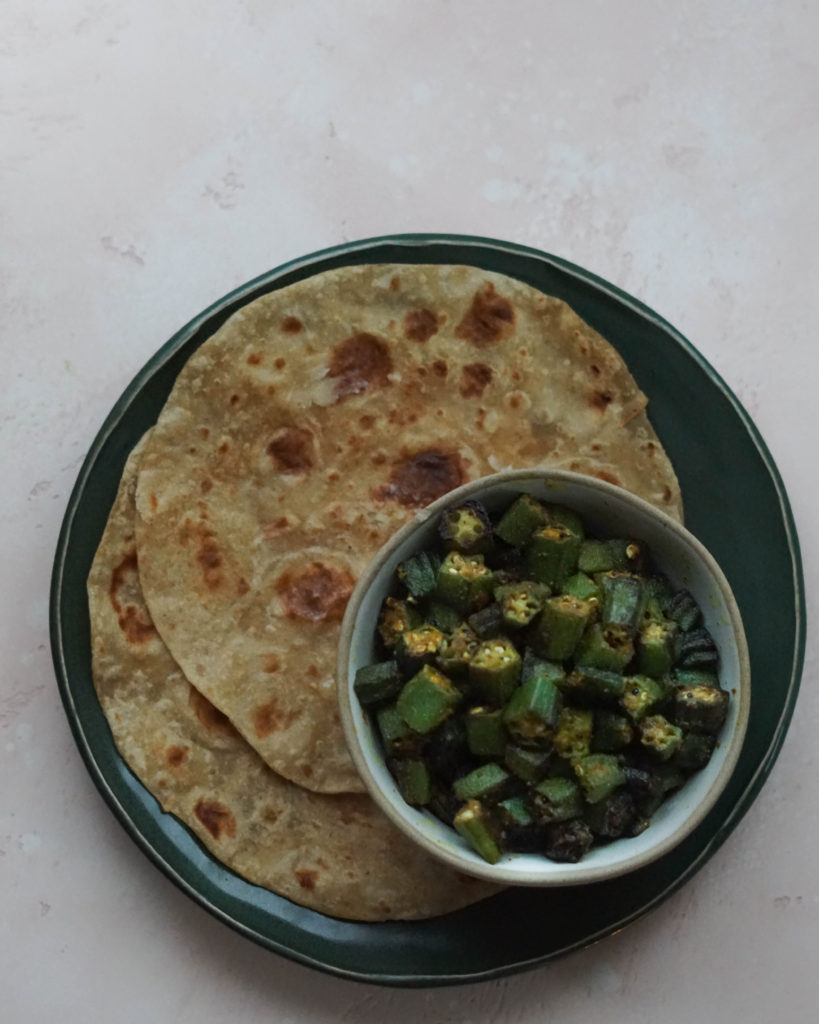 Indian bhinda nu shaak, a Gujarati dish on a green plate with rotis on the side.