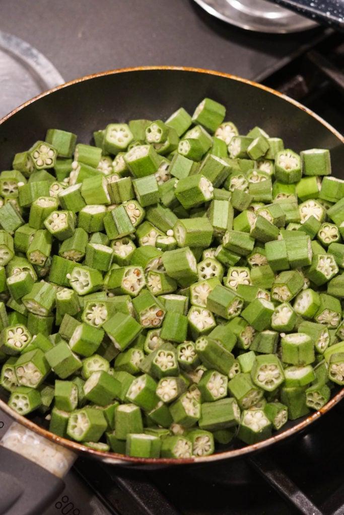 Cut okra in a large pan.