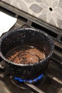 Mustard seeds in pan in heated oil.