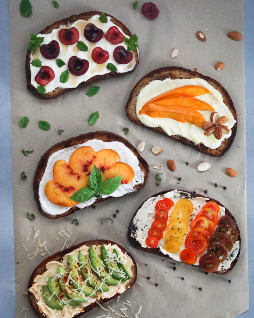Five Breakfast Toasts on parchment with fruit and garnish
