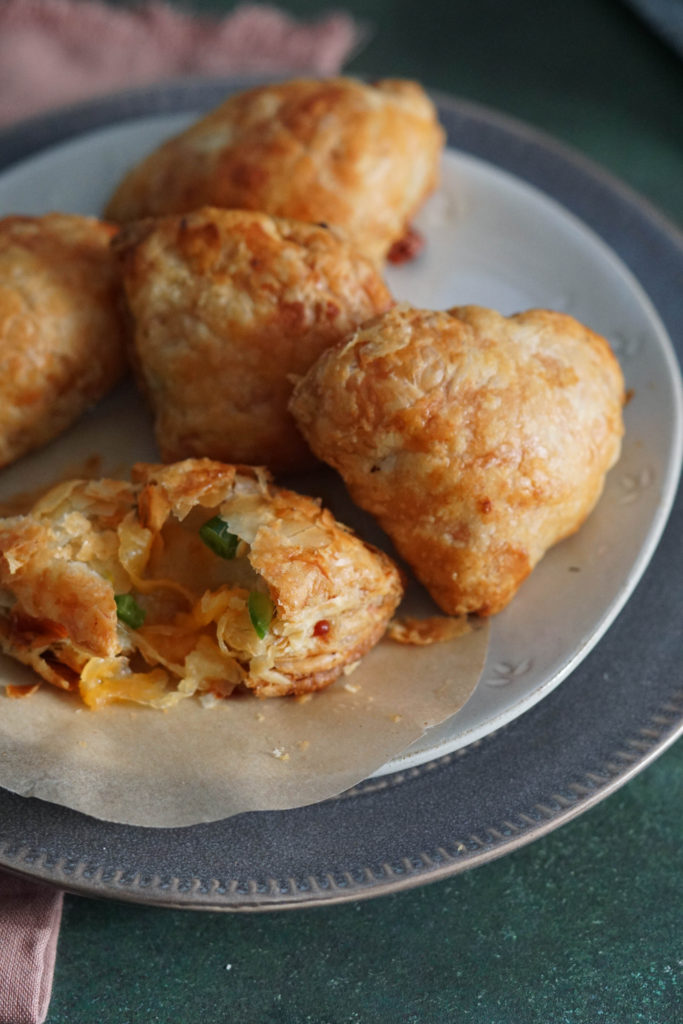 baked samosas with puff pastry on a white plate.