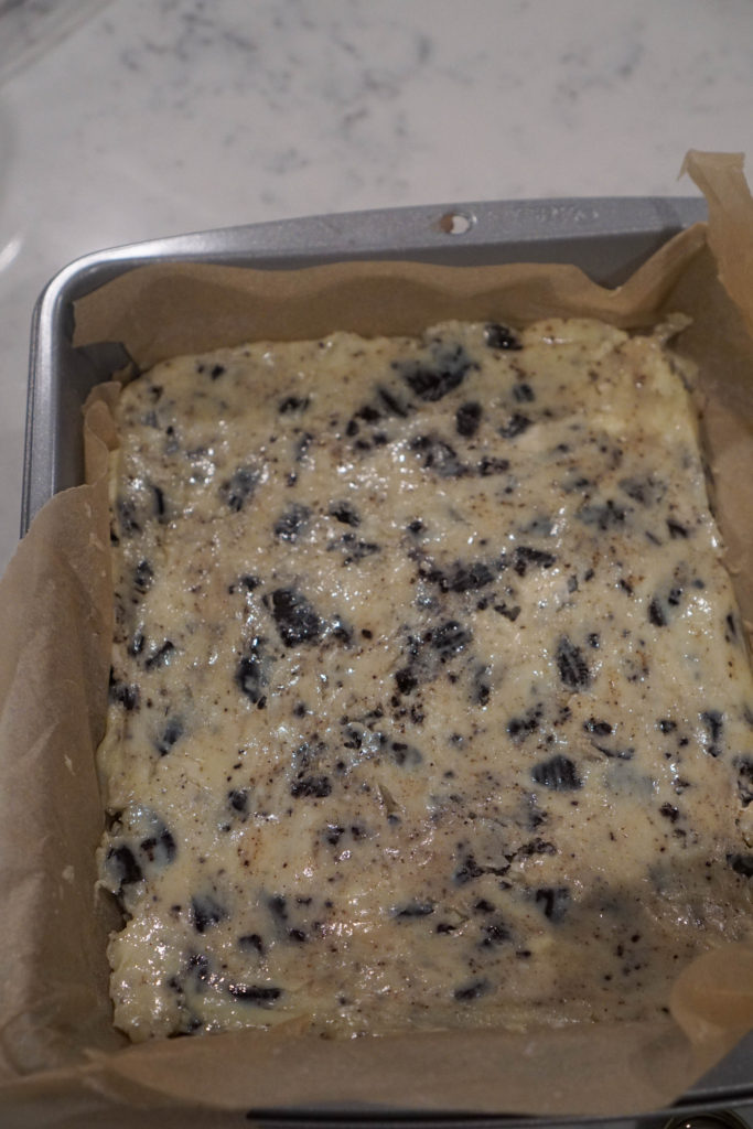 Cookies and cream burfi spread in parchment lined pan.