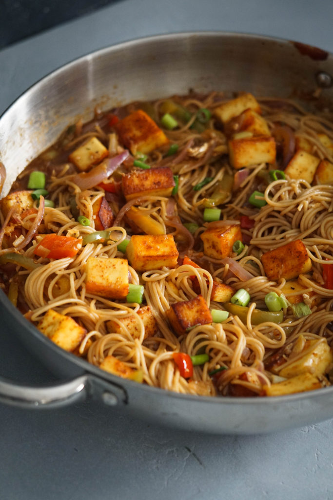 chilli paneer noodles in a wok