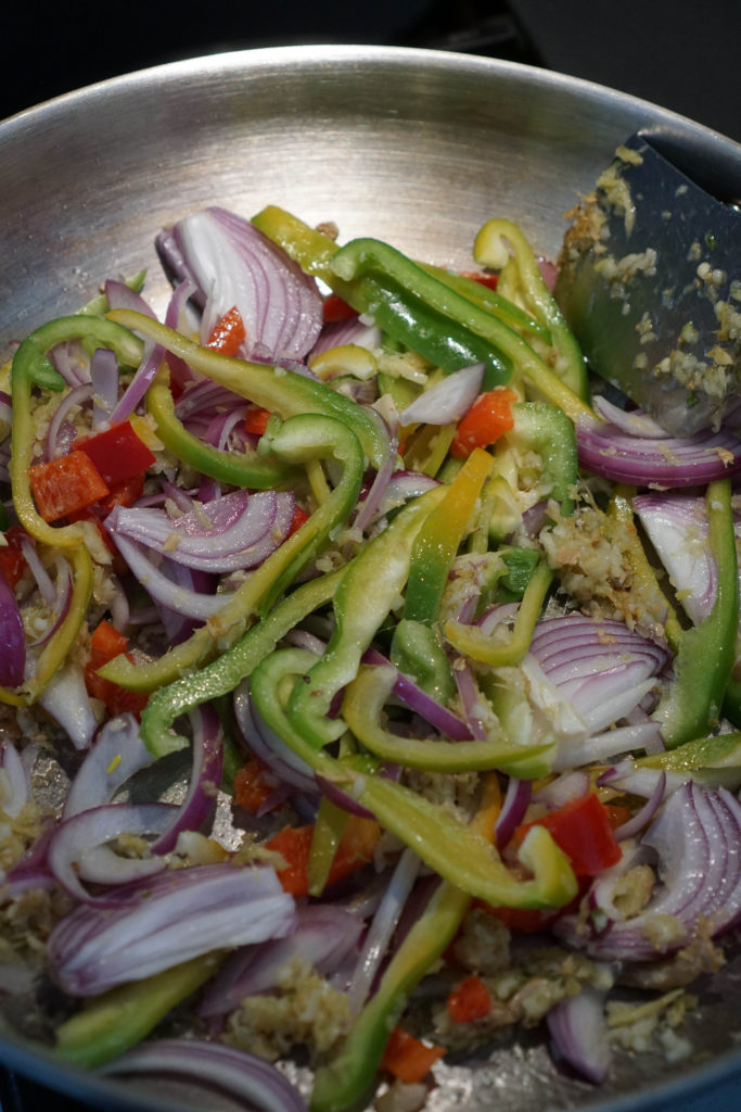 Onions, bell peppers, ginger, garlic in a stainless steel wok.