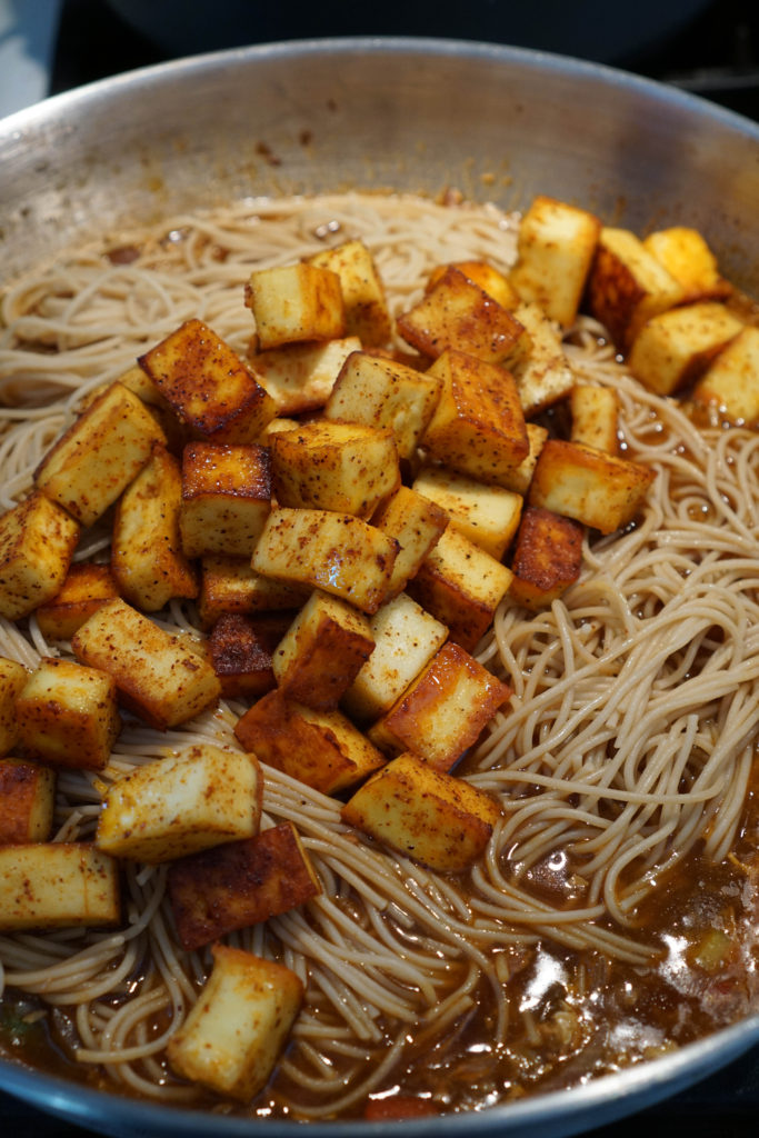 Noodles and paneer added to chilli paneer gravy.