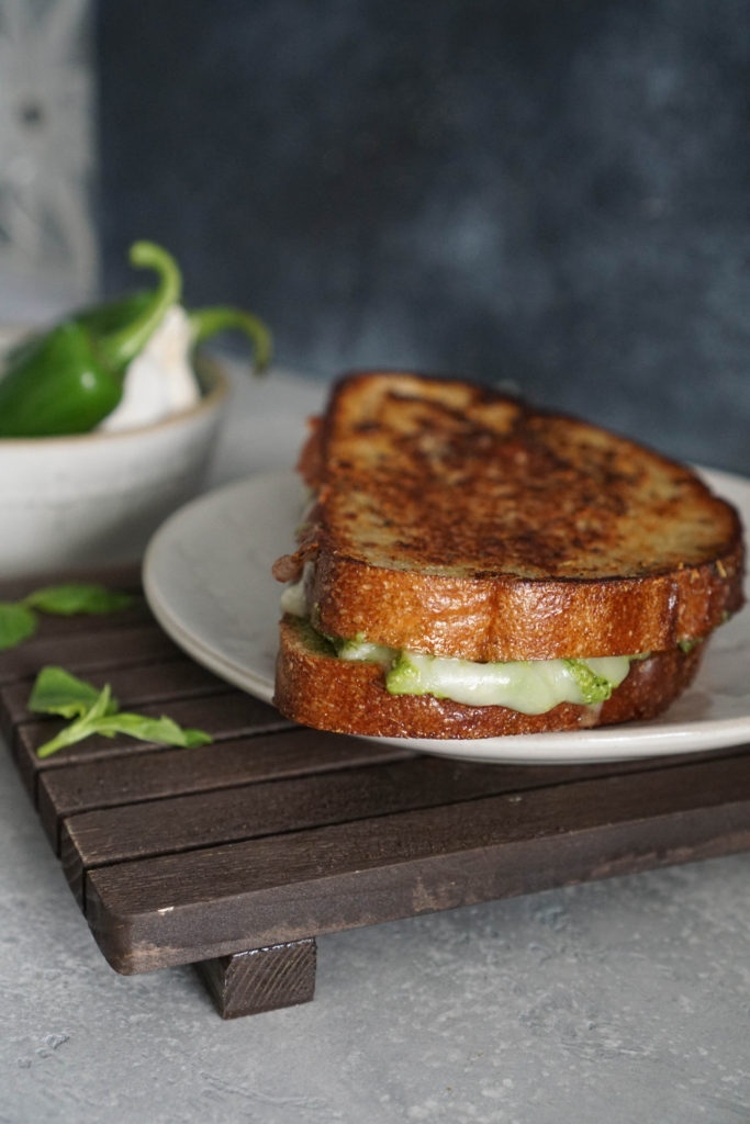 jalaepno pesto grilled cheese on a white plate on a wooden board.