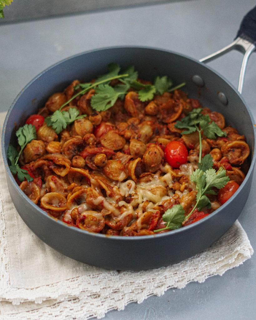 indian spicy pasta in a pan garnished with cilantro