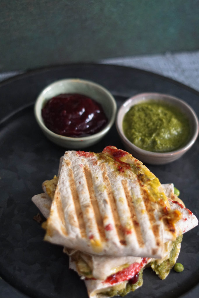 samosadilla with chutneys on the side all on a gray plate