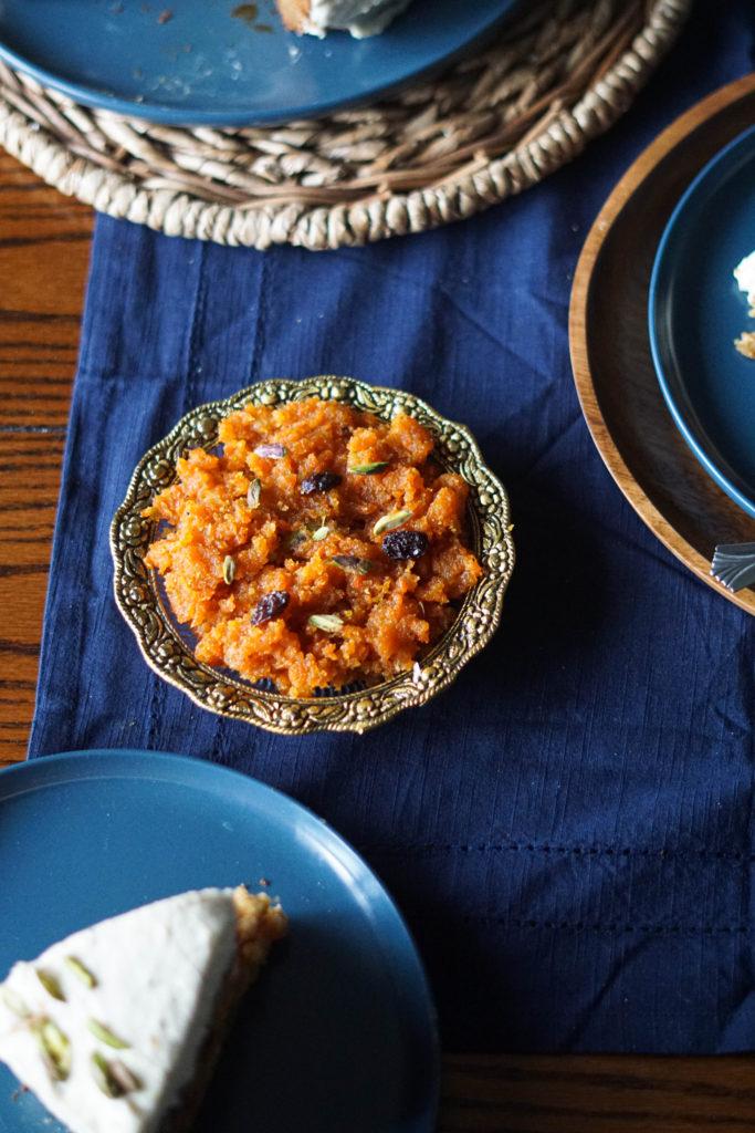 vegan gajar ka halwa on a table with blue tablecloth with other plates