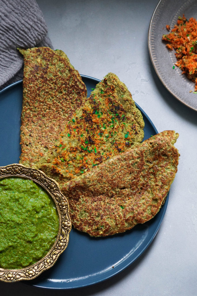 Moong dal pudla with vegetables on a blue plate with cilantro chutney on the side.