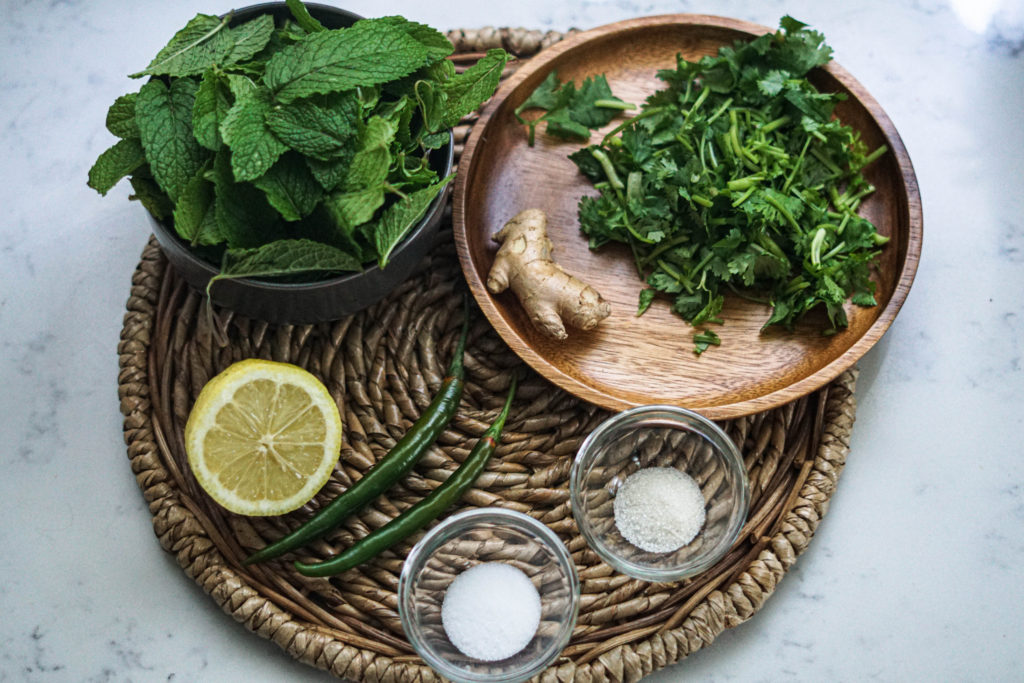 Mint pudina chutney ingredients in bowls on a bamboo plate