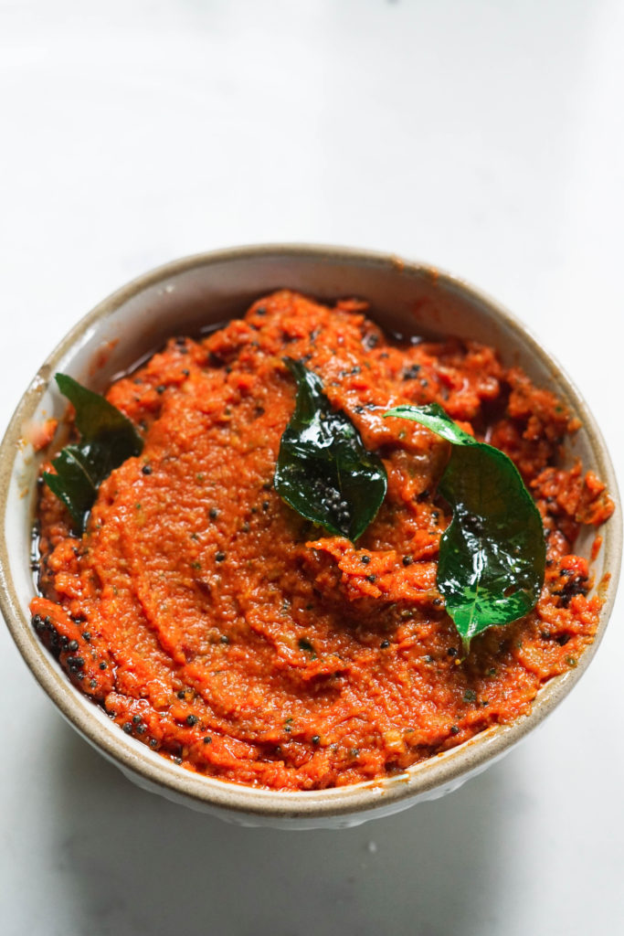Garlic Tomato Chutney in a bowl with curry leaves on top