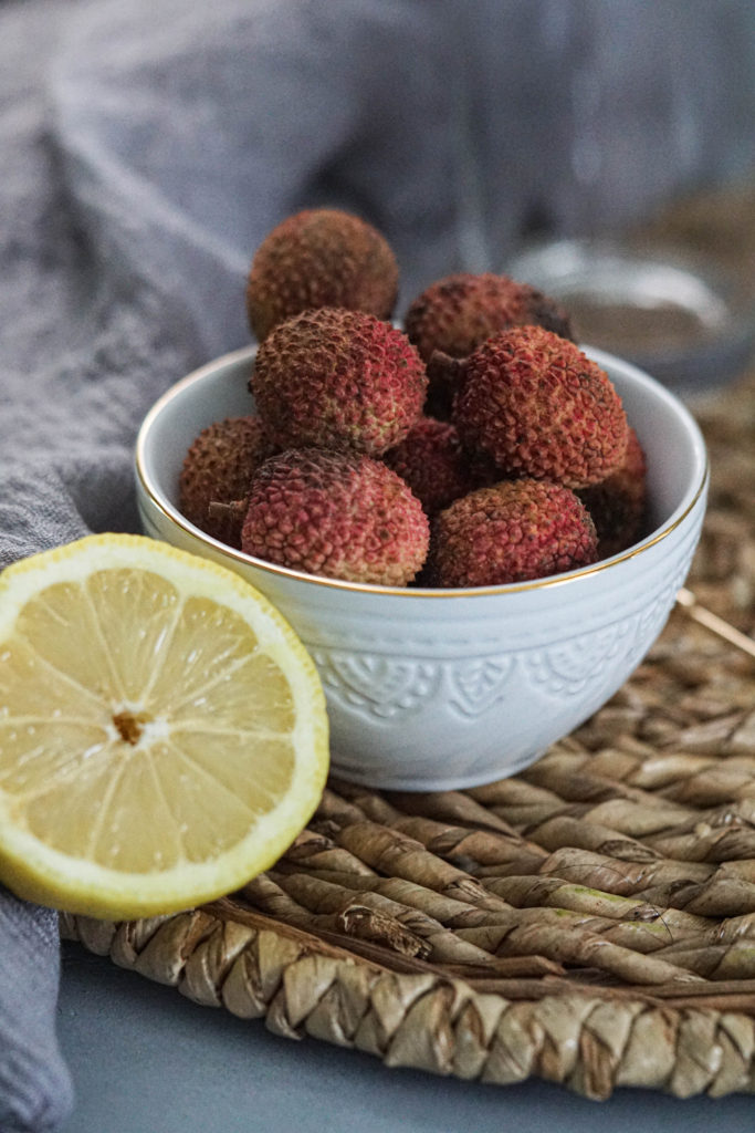 bowl of lychees with a sliced lemon to the side