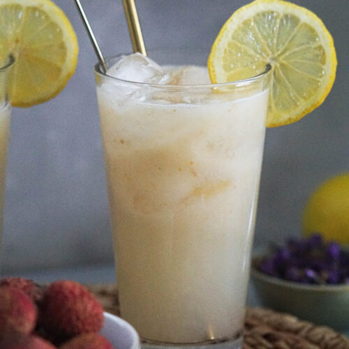 litchee juice lemonade in a glass topped with a lemon slice and lychees in a white bowl on the side.
