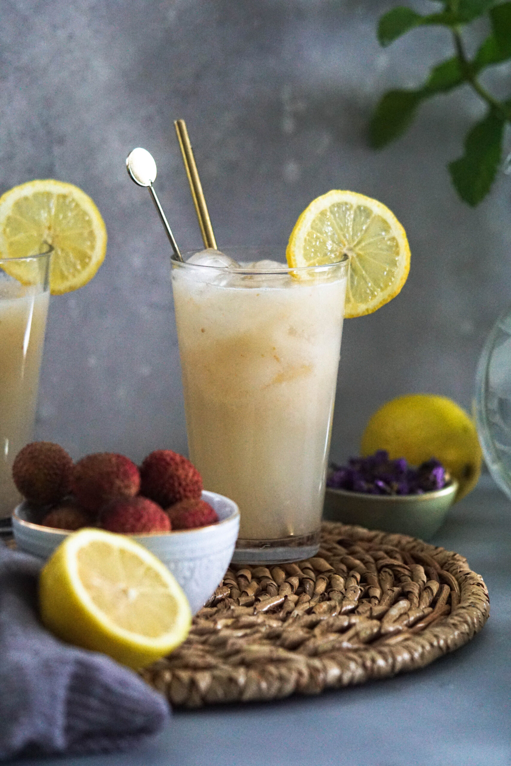 Lychee lemonade in a tall glass with stirrer and lemon slice and lychees in a bowl off to the side