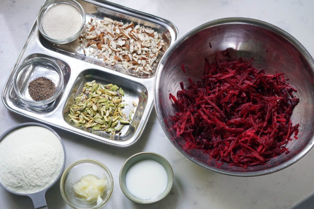 beetroot halwa ingredients in bowls and a plate on marble top.