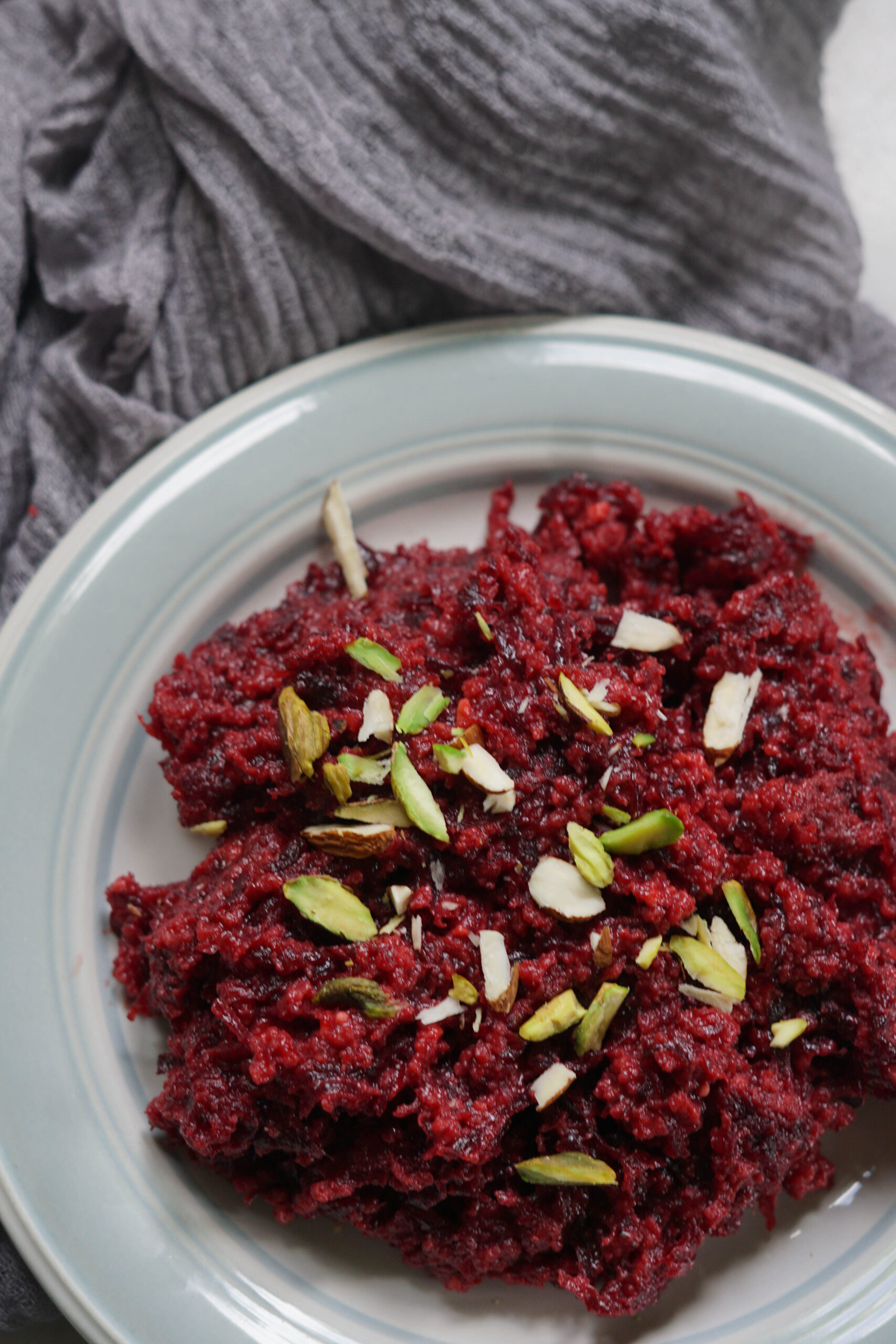 beetroot halwa on a plate with pistachios garnished on top
