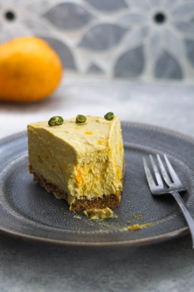 Mango cheesecake slice on a gray plate with a bite taken out and a fork to the side.
