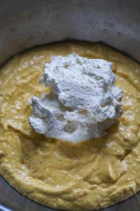 Whipped cream added to mango cheesecake mixture