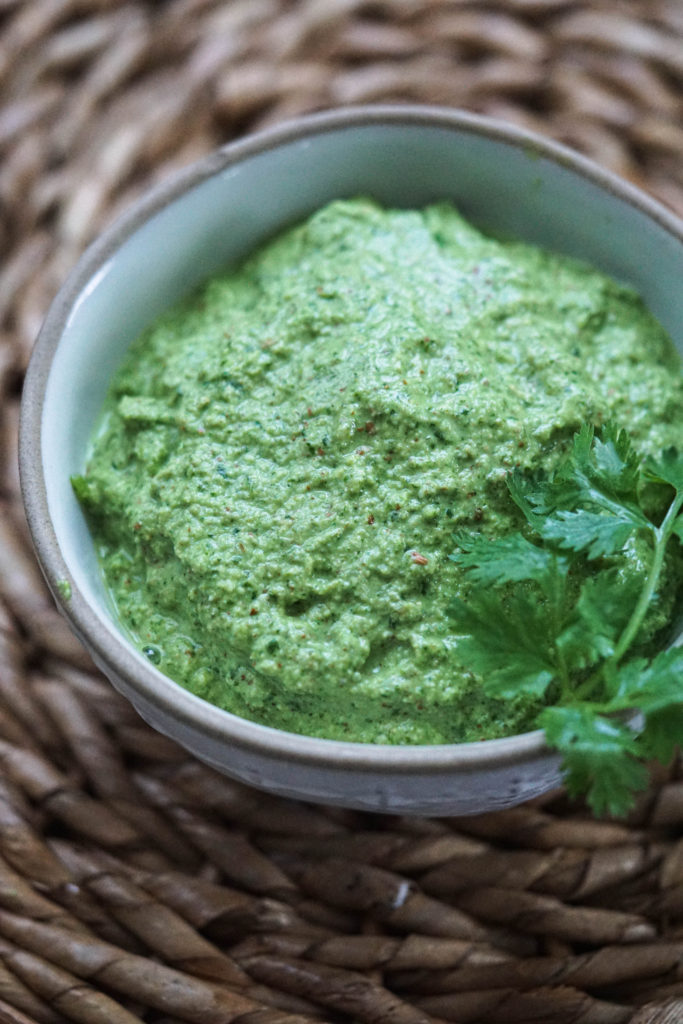 Bright green Indian coriander chutney in a small white bowl on a bamboo placemat.