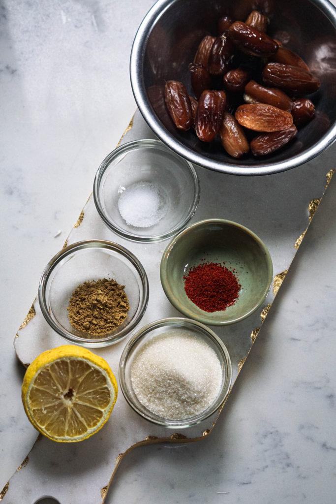 Khajoor ki chatni ingredients in small bowls on a marbletop board.