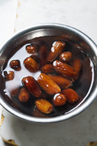 Dates soaking in warm wtaer in a steel bowl.