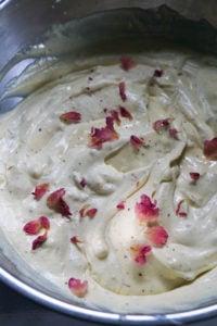 Gulab jamun ice cream mixture in a steel bowl with rose petal garnish.
