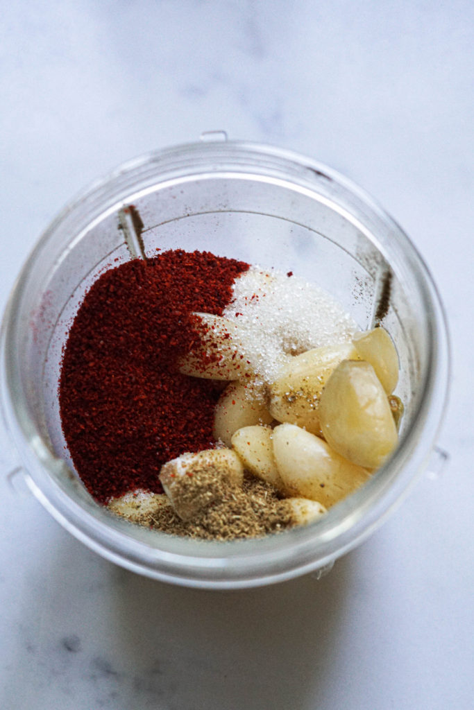 Garlic cloves, spices and water in a blender jar.