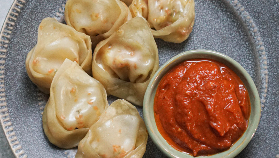 Paneer momos on a gray plate with chutney in a small bowl to the side.