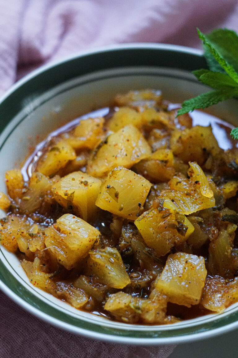 Pinapple chutney in a bowl with mint as garnish.