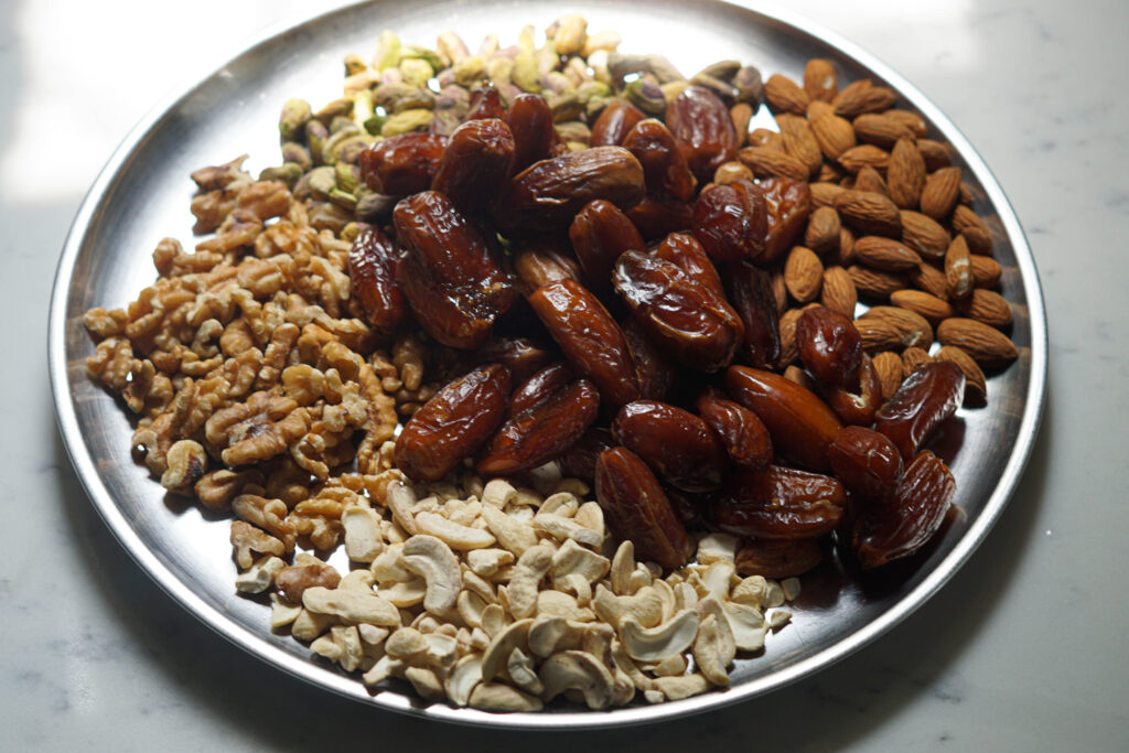 Dates, cashews, almonds, pistaschios and walnuts on a plate.