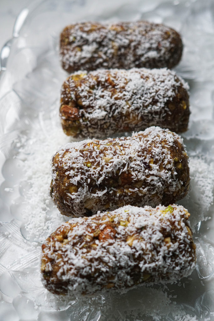 Date nut rolls barfi rolled in dessicated coconut on a glass plate.