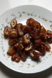Chopped dates in a leaf vine designed white plate.
