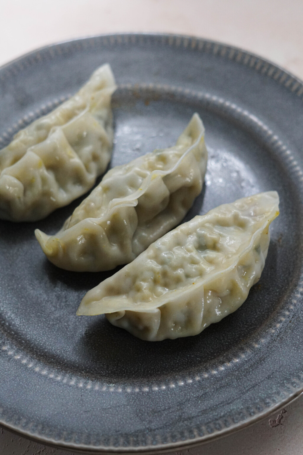 Steamed vegetable momos on a gray plate.