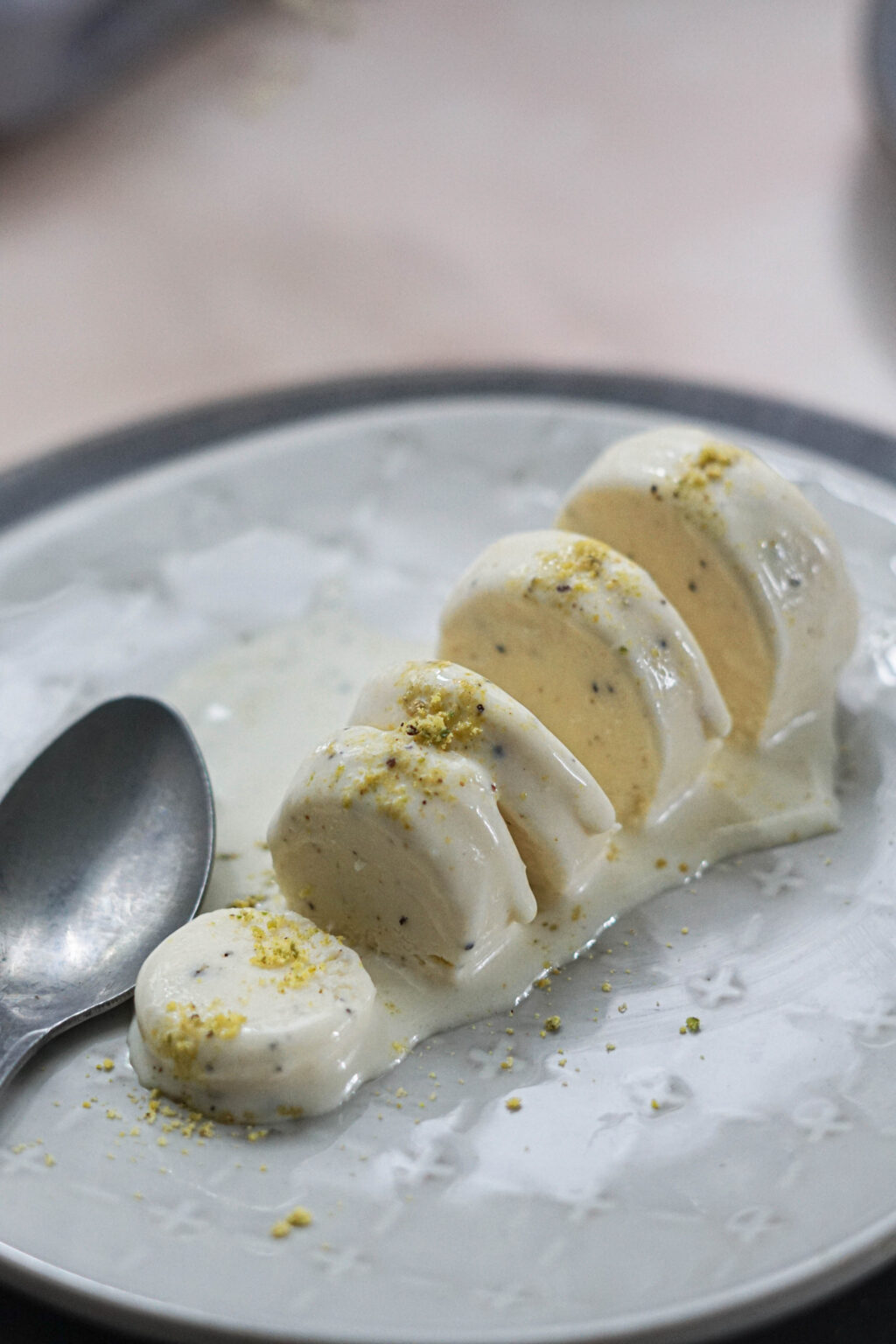 Kulfi with khoya or mawa on a white plate with pistaschio sprinkled on top with a spoon to the side.