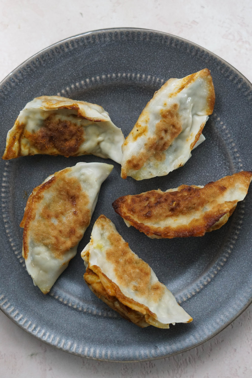 Five pan fried paneer momos on a gray plate.