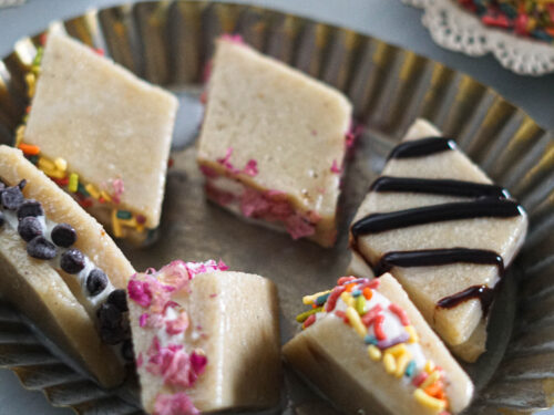 Kaju katli pieces sandwiching ice cream with various topins such as sprinkles and chocolate chips.
