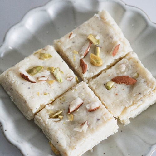 Four milk barfi made with milk powder squares on a white fluted plate.