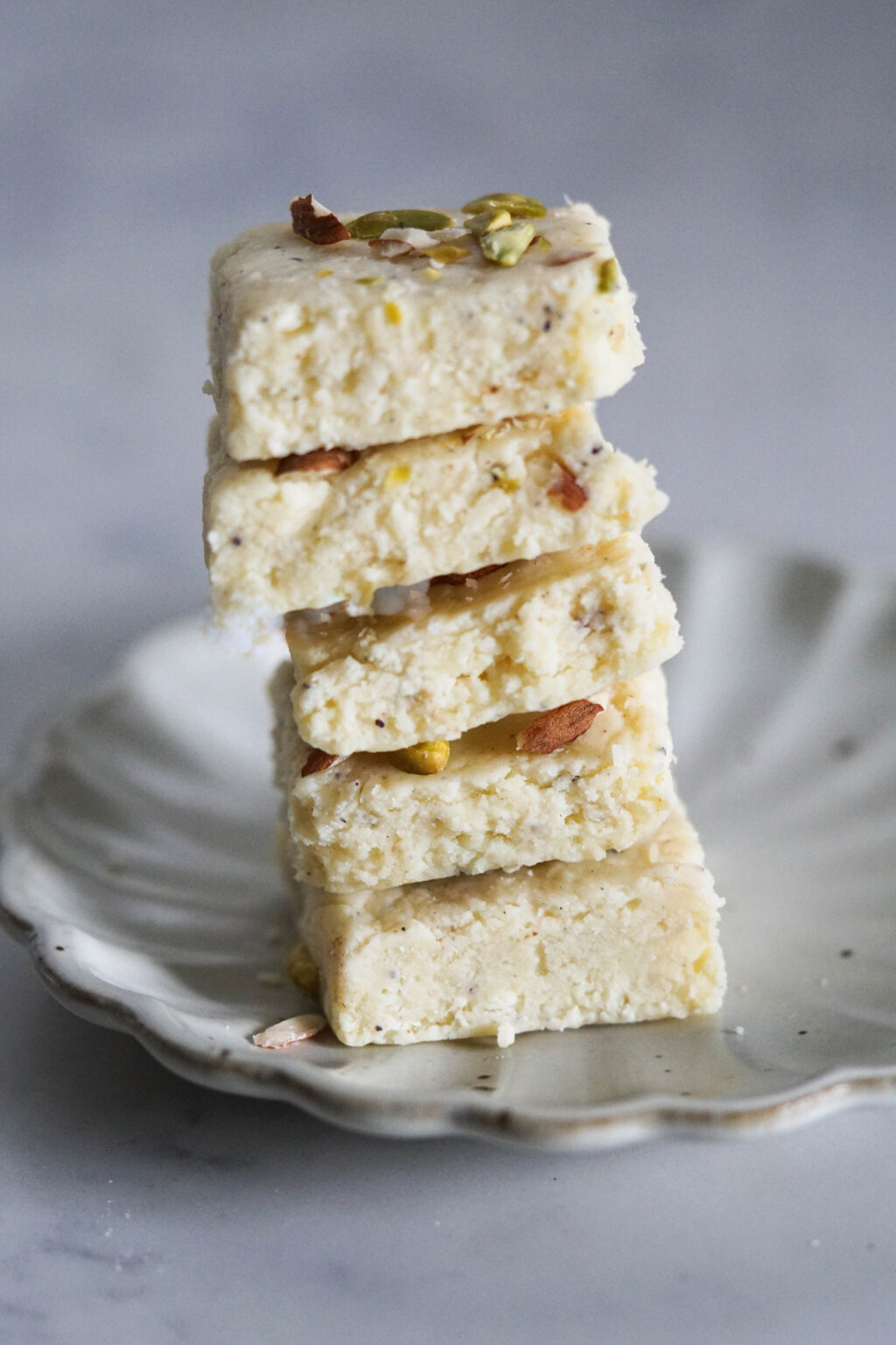 Stack of white milk powder burfi on a white fluted plate.