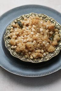 Sabudana khichdi in an ornate gold bowl on a gray plate.